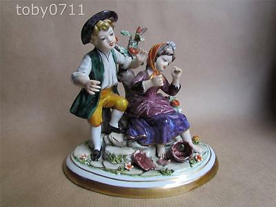 CAPODIMONTE NAPLES FIGURINE OF A BOY AND GIRL SITTING ON A ROCKY OUTCROP