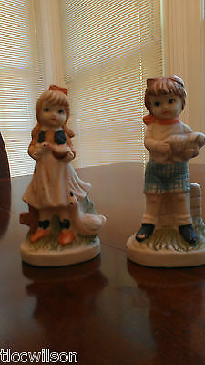 Unsigned figurines boy with rabbit and girl with goose vintage figures set of 2