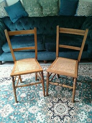 2 Edwardian satinwood chairs with turned legs and wickerwork seats