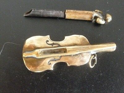 Antique Violin in brass  holding a pencil