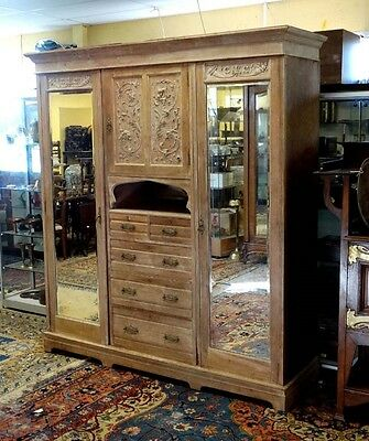 Antique C19th triple armoire with bevel mirror doors drawers and carved front
