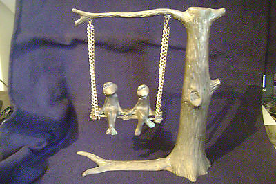 Brass Frogs On Swing Holding Hands