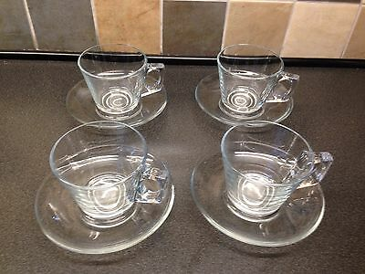 Set of four glass cups and saucers