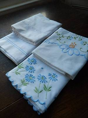 Four vintage white cotton pillowcases with blue themed embroidery