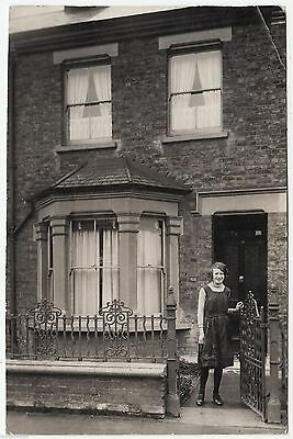 A LADY AT THE GATE OF A TERRACED HOUSE  - c1910s era Real Photo postcard