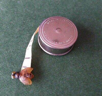 White Metal Tape Measure with bee at end of Tape.