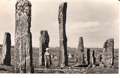 RP 1959 Lady stands amongst the CALLANISH STONES, Isle of Lewis, houses at back