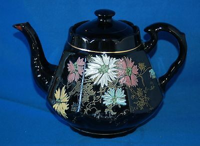 Vintage floral decorated teapot with black background