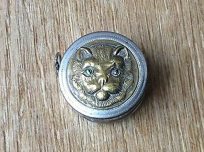 Vintage white metal retractable tape measure with a brass cat face