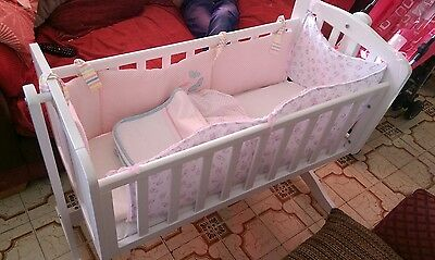 white wooden rocking crib with bumpers and some bkankets