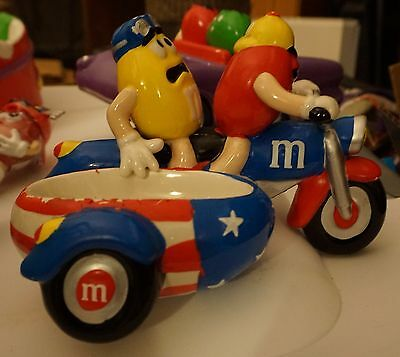"M&M ceramic candy dish featuring characters ""Red"" and ""Yellow"" on a motorcycle"
