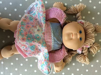 2004 Cabbage Patch Kid Doll. Blonde hair, pink dress, signature right cheek