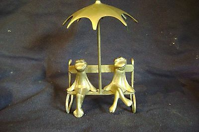 Brass Frogs Seating On Bench / Umbrella