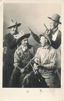 c1912 RPPC Four Cowboys with Pistols, Knives, a pipe and Hats Photo Postcard