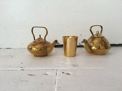 pair of miniature brass teapots and cup