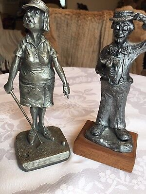 2 silver funny figurines a man with flowers and a women playing golf