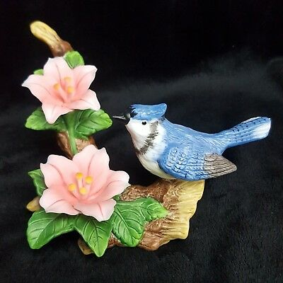 Porcelain figurine blue jay perched on a tree branch with pink flowers