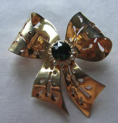 Vintage gold tone knot brooch with green rhinestones