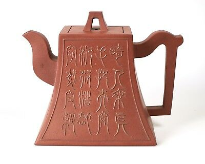 Antique Chinese Yixing teapot with raised inscription.