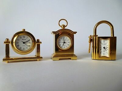 A collection of three miniature brass clocks.