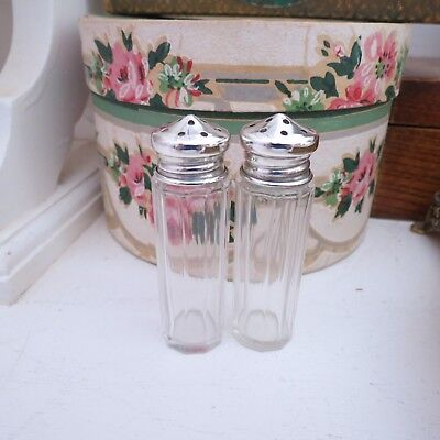 Two small cut glass pepper/salt pots with silver lids