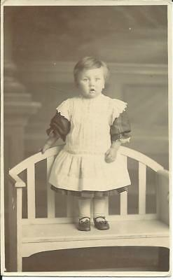 TODDLER STANDING ON BENCH (REAL PHOTOGRAPHIC POSTCARD) c1930