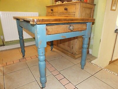 A Victorian pine kitchen table with original castors