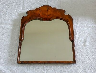 Antique walnut wall mirror with carved top and original bevelled silvered glass
