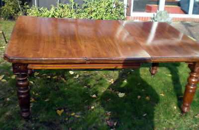 An extending solid American walnut dining table c.1880, seats eight