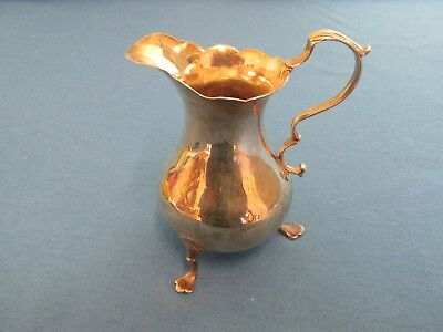 "Small silver jug with decorative feet Measures 4.25"" high 2.5"" wide"