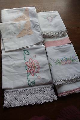 Seven (7) vintage white cotton pillowcases with coloured embroidery or trim.