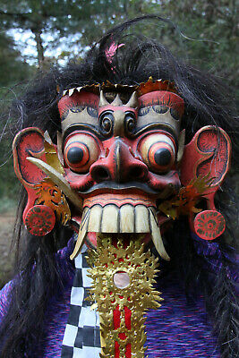 Imported, hand-carved wooden mask with long black hair.