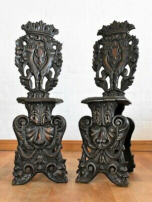 Antique pair of heavily carved hall chairs