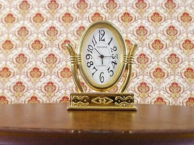 A beautiful brass quartz clock made in the style of a ladies dressing table