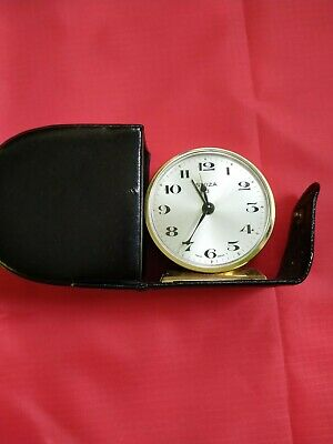 A vintage swiza swiss brass travel alarm clock in leather case.