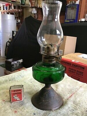 Antique oil lamp, dark green  glass and a cast base with kookaburra motif