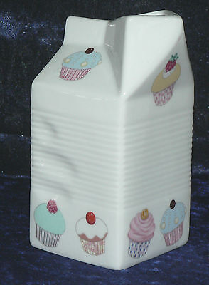 Milk carton shaped jug off white ceramic decorated with colourful cupcakes