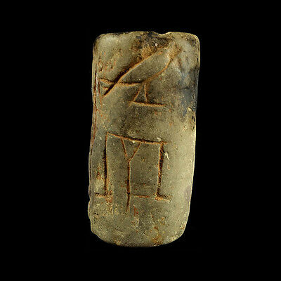 A limestone seal engraved with Horus falcon above house and other glyph a7971