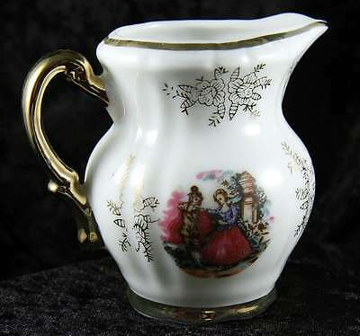 milk jug  in white 3 inches tall  with lady & gentleman detail