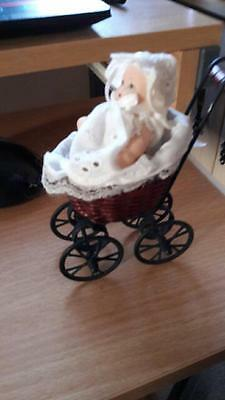 Small metal pram and doll