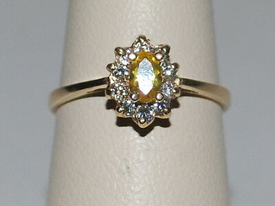 10K Gold ring with a yellow gemstone and halo of diamonds