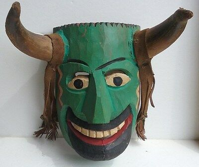 Carved wooden mask horned wall decoration.