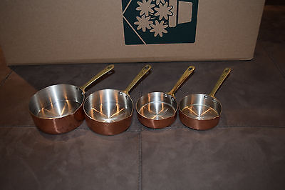 Set of 4 vintage copper measuring cups, tin lined with brass handles.