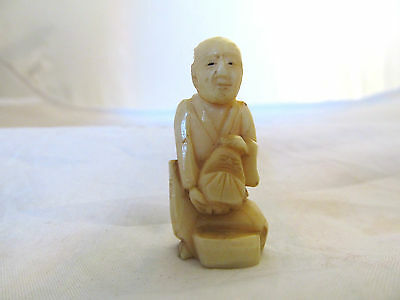 collectible old japanese carved netsuke, a man sitting with a small bag unsigned