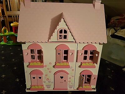 pink wooden dolls house with furniture and characters