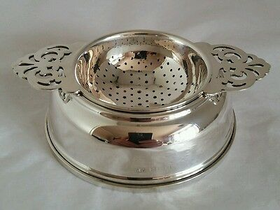 A sterling silver tea strainer and stand. Birmingham 1958.By William Suckling Lt