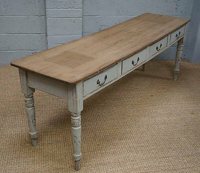 A 20th century white painted pine serving table with 4 double sided drawers.