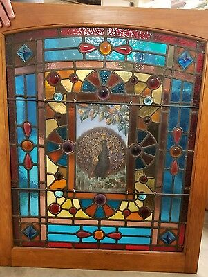 Tiffany Studios leaded stained glass window with a peacock in the middle and geo