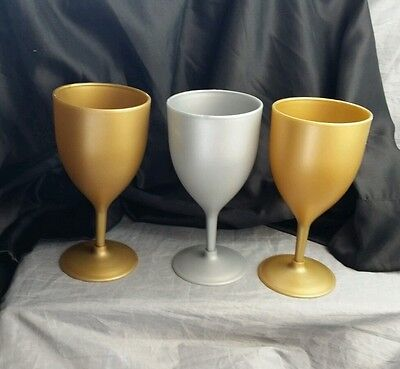 3 plastic collectable silver and gold colored wine glasses