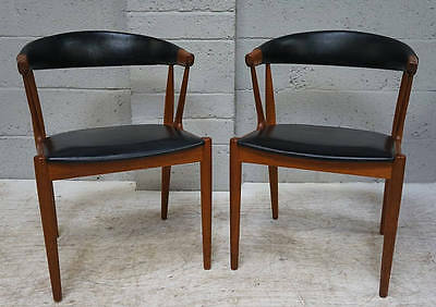 A pair of 20th century teak and black leatherette open arm chair,made in Denmark